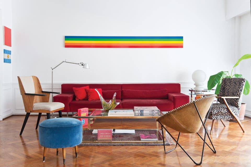 En el living, una obra de Sergio Avello y dos mesitas de anticuario; un sillón redondo (Feria Tristán Narvaja, Montevideo), un banquito americano (Mercado de Pulgas) y un sofá realizado a medida. La silla, que reitera los tonos de la serigrafía de Alexander Calder, es un prototipo de José Strier, de.  /Pompi Gutnisky