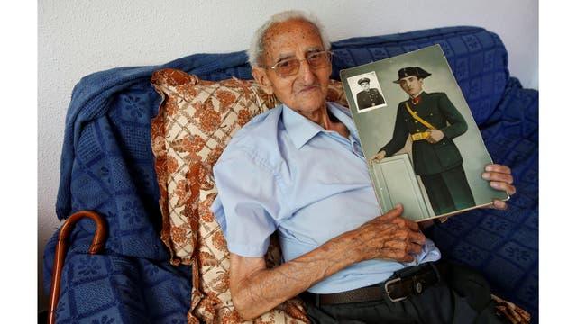 Gumersindo Cubo, 101, posa para un retrato con una foto de sí mismo cuando era joven, en su casa de Casavieja, Avila, cerca de Madrid, España.