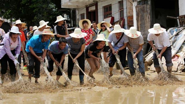 La gente limpia el barro de una calle inundada en Luizhou, provincia de Guangxi
