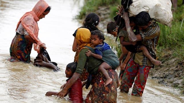 Refugiados Rohingya lavan su ropa mientras cruzan un canal en Teknaf, Bangladesh