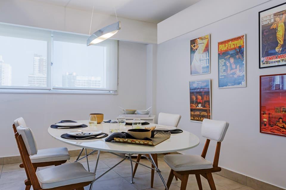 La mesa oval, para seis comensales, tiene patas cromadas y tapa de laca (Manifesto). En un anticuario, se compraron las sillas vintage, que se retapizaron en cuero. Lámpara 'Slimm Cielo' de cuarzo (Onic Iluminación).  Foto:Living /Daniel Karp