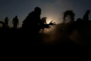 Un manifestante palestino intenta apagar un incendio provocado por objetos arrojados por aviones no tripulados israelíes durante una protesta contra el traslado de la embajada de EE. UU. A Jerusalén