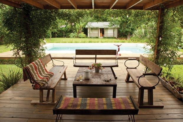 En el deck que avanza sobre el césped, juego de living con sillas muy camperas hechas de madera recuperada y una mesa con una base de varillas de alambrado (todo de Villatte).  Foto:Living /Javier Csecs
