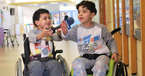 El niño de la derecha de la imagen utiliza la silla de rueda de Wheelchairs of Hope