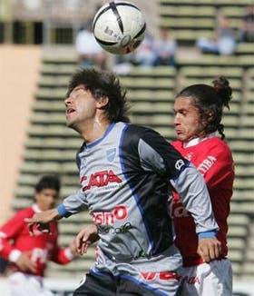 El volante Diego Villar, de Godoy Cruz, le gana en el salto a Cristian Celay, de Huracán