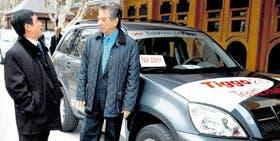 El vicepresidente mundial de Chery, Zhou Biren, dialoga con Macri junto a un Tiggo fabricado en Uruguay