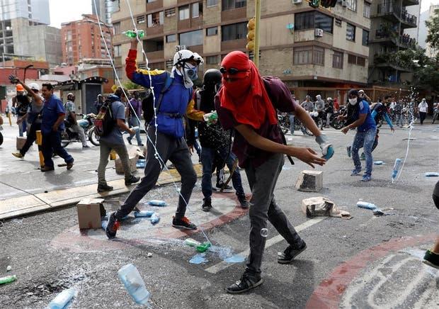 Los manifestantes destruyen productos de limpieza saqueados durante una marcha