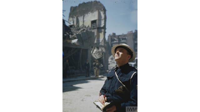 Un miembre de Air Raid Precautions (ARP) inspecciona los edificios dañados en Holborn, Londres