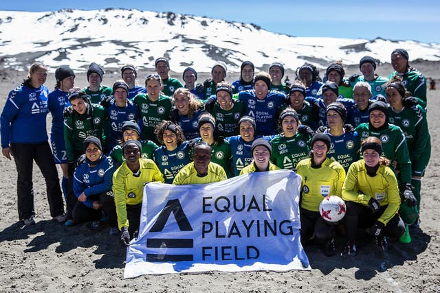 Las jugadoras posan en la cancha con la bandera de Equal Playing Field. FOTO: Dana Rosiger.