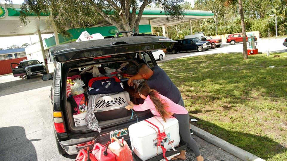 Isabel Márquez carga su auto, regresará a su casa luego del paso del huracán. Foto: AFP