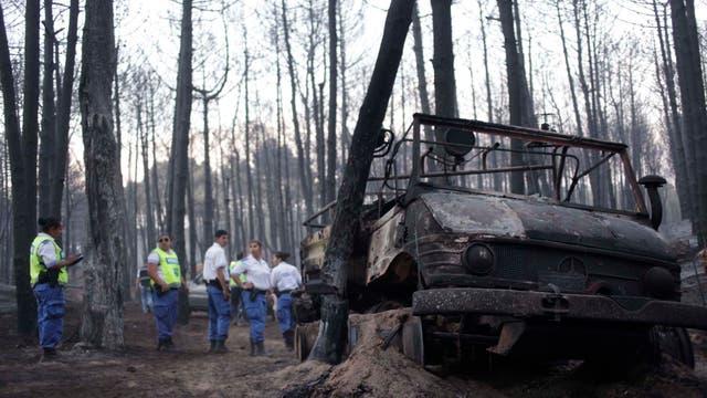 Un vehículo que fue alcanzado por el fuego permanece al lado de un árbol. Foto: Télam
