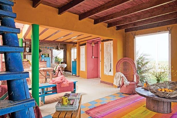 En la zona del living, sobre la vibrante combinación en damero, una alfombra tejida a mano ( Husos y Costumbres). Ese espacio se armó en torno al hogar, que también se usa como parrilla..