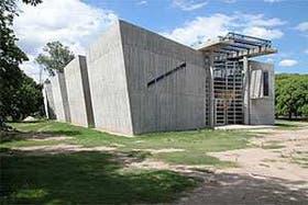 Una vista del ingreso del edificio de la Escuela de Posgrado de Ciencias Económicas, con la nave central vidriada que se prolonga en los extremos formando la cubierta del acceso