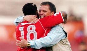 Bertoni, de frente, y Castillo, de espalda, se funden en un abrazo ganador; los Rojos triunfaron como locales y el colombiano fue la figura