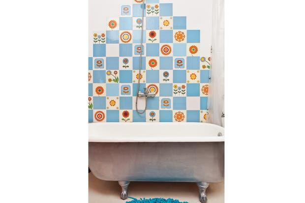 Para no tapar la presencia de su diseño, la cortina de baño se recoge hacia un costado. En esa pared incorporó el duchador ($329, Aquaflex) y, a los pies, una alfombra azul ($120, Tienda Palacio).  /Javier Picerno