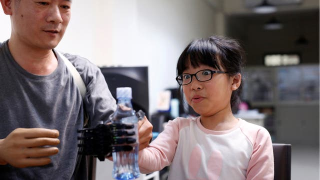 Angel Peng, de 8 años, durante las pruebas de su mano impresa en 3D diseñada y construida por el ingeniero Chang Hsien-Liang, en Taoyuan, Taiwan.