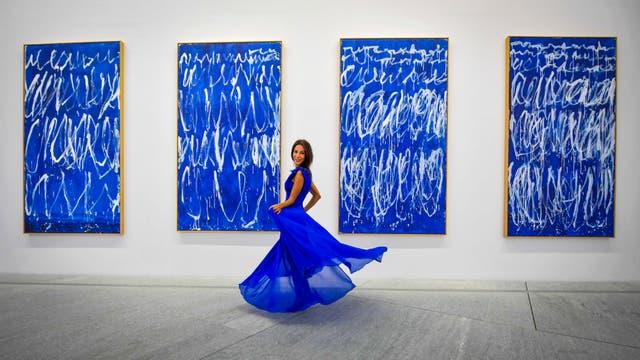 """Una mujer posa frente a una parte de una serie de nueve paneles titulados """"Untitled I-IX"""" del pintor estadounidense Cy Twembly"""