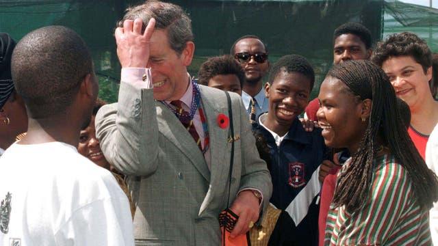 El príncipe Carlos comparte una broma con los residentes durante una visita al municipio de Nyanga a las afueras de Ciudad del Cabo