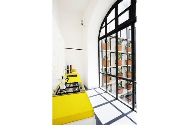 Un resultado brillante: una cocina con un ventanal enorme aprovecha su condición luminosa y se multiplica a través de esta mesada en un amarillo profundo. | Foto: design-milk.com.