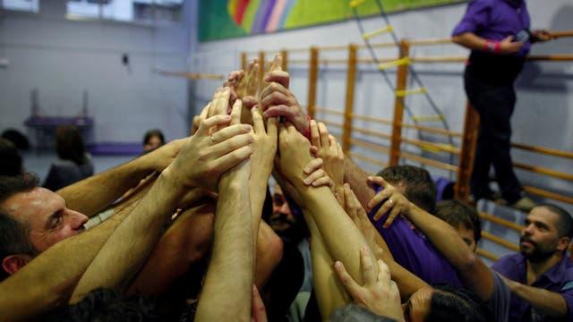 En un colegio, un grupo de personas alzan sus manos a favor del referéndum. Foto: Reuters
