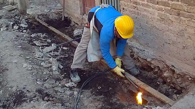 Un operario trabaja para remover una vía escondida bajo tierra