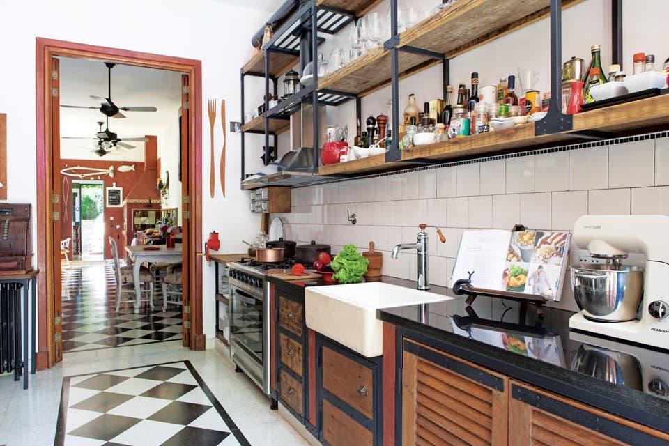 Para hacer los muebles de cocina (Horacio Manzione) se usaron maderas recuperadas y puertas recicladas. La mesada se hizo con doble mármol negro. Bacha apoyada con grifería vintage 'FV 424' (Barugel) y batidora/ amasadora 'Smartchef' de Peabody (Garbarino).  Foto:Living /Javier Picerno
