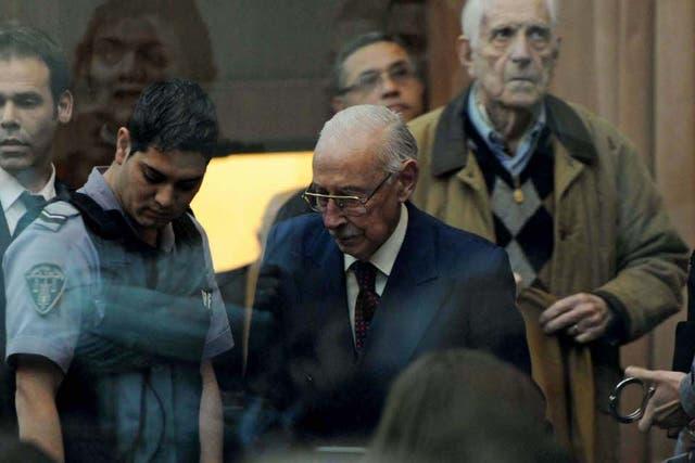 Videla ingresa a la sala de audiencias de los tribunales para escuchar la histórica sentencia, seguido de Bignone