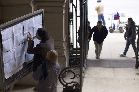 Varias personas se buscan en los padrones para poder votar. Foto: EFE