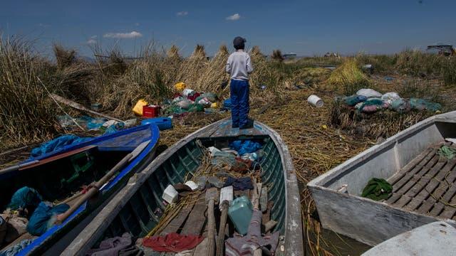 Un muchacho observa desde un barco de pesca lleno de desperdicios, en la orilla del lago Titicaca en Kapi Cruz Grande, en la región de Puno de Perú.