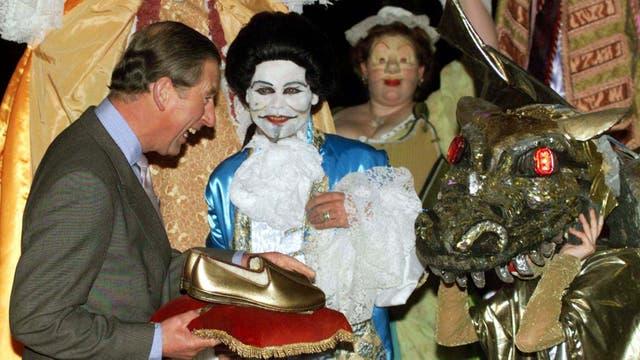 Bromeando con miembros del grupo de teatro Creature Feature cuando le presentaron un 'Over Fifty Kit', que consistía en un par de zapatillas de oro, una pipa de oro y su certificado que lo aceptaba en el club de más de cincuenta cuando llega al Palacio de Buckingham de Londres, el viernes