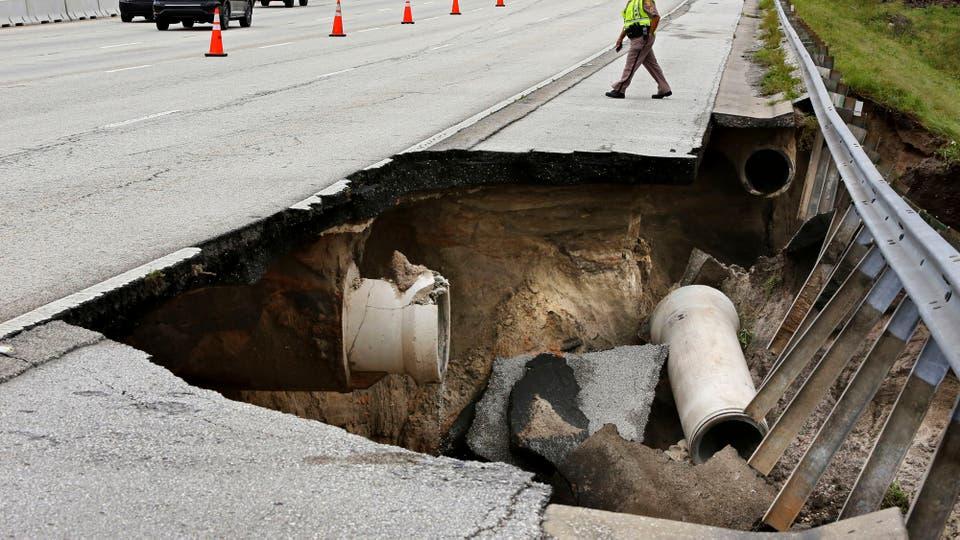 Un enorme agujero se abrió tras colapsar la tierra debajo de una autopista. Foto: AP