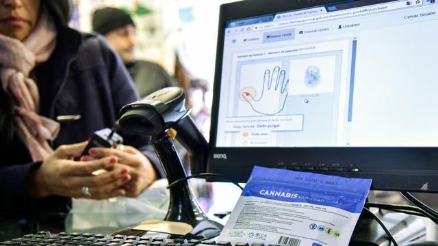 Una mujer coloca su pulgar en un sistema de reconocimiento de huella digital en una farmacia de Montevideo, Uruguay. Foto: Pablo Abarenga