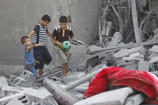 Chicos palestinos caminan sobre los escombros de un edificio en el sur de Gaza. Foto: AFP