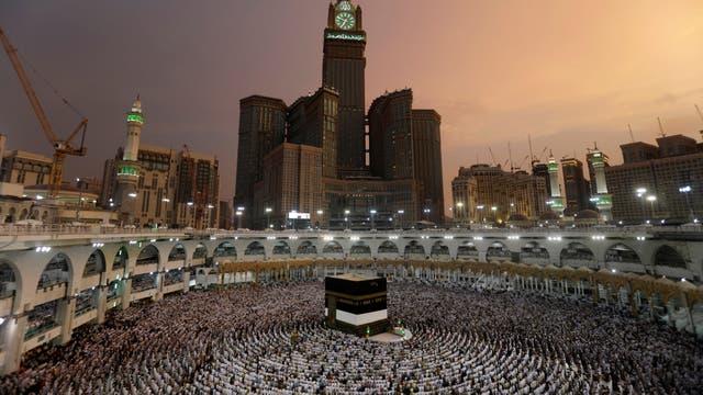 Vestidos de blanco, con las manos alzadas alcielo, los peregrino rezan en La Gran Mezquita