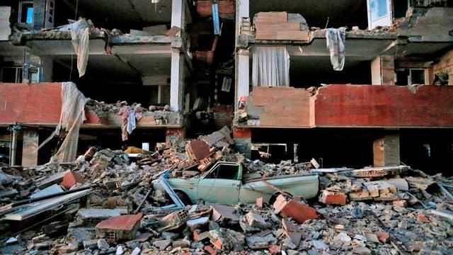 un vehículos aplastado por los escombros que cayeron de un edificio que colapsó tras el terremoto