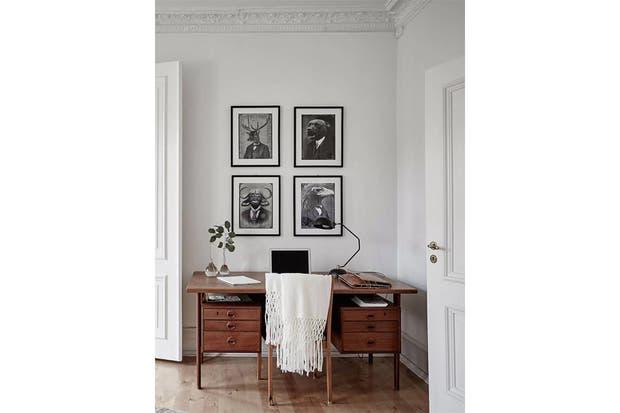 Para los más clásicos, un escritorio y una silla de madera lustrada con pocos elementos decorativos. Las cuatro láminas en blanco y negro enmarcan el sector.  /Cocolapinedesign.com