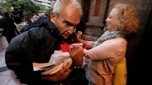 Un hombre ingresa a una escuela con las boletas que servirán en el referéndum. Foto: Reuters