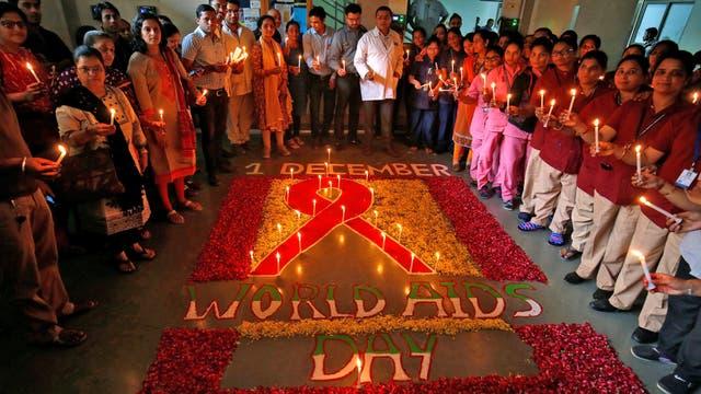 En Ahmedabad, India, varias personas se reúnen para conmemorar el Día Mundial de la Lucha contra el VIH