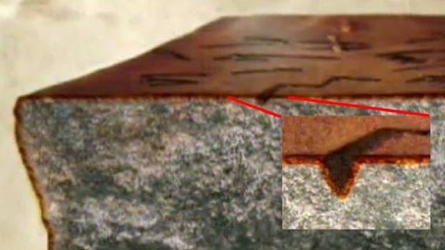 La pátina, esa capa que se forma sobre las rocas a lo largo de mucho tiempo, no sólo era continua sino que estaba presente en los huecos hechos por las letras, demostrando que habían sido hechos en el pasado lejano.