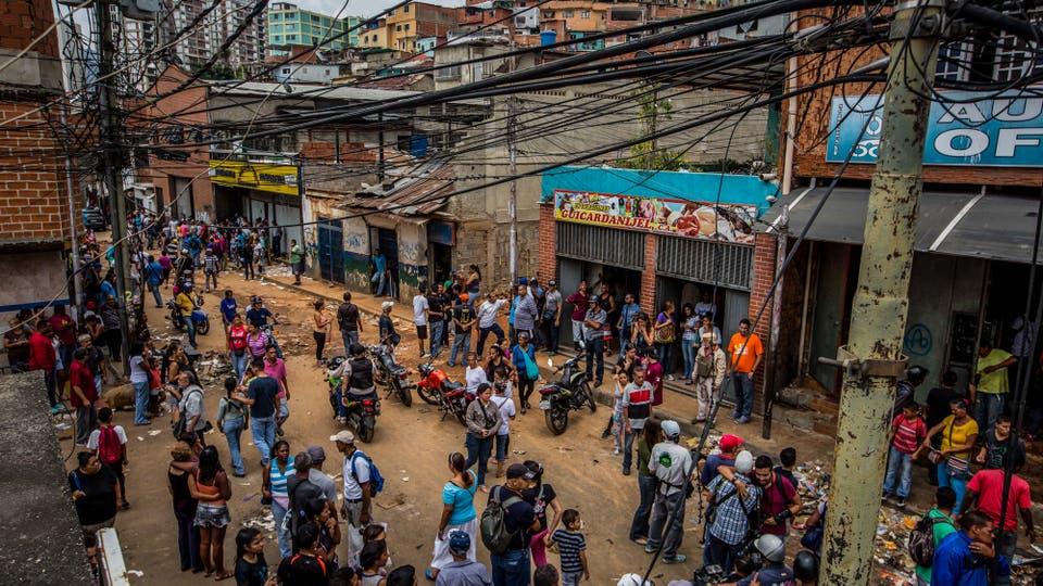 Docenas de personas en las afueras de varios locales que fueron saqueados anoche en el barrio de El Valle, Caracas. Foto: EFE / Miguel Gutierrez