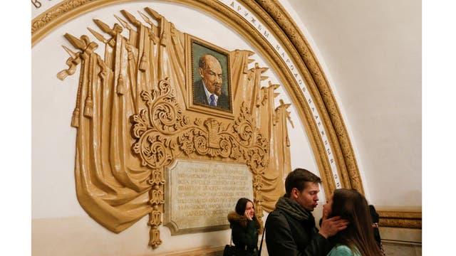 Un par de besos delante de un mosaico que representa el fundador del estado soviético Vladimir Lenin en la estación de metro Kievskaya en Moscú, Rusia