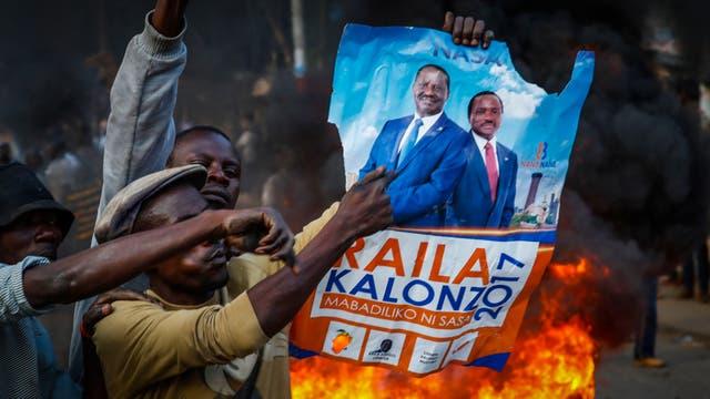 Partidarios del líder de la oposición, Raila Odinga, sostienen el poster de su candidato en Kibera, Nairobi