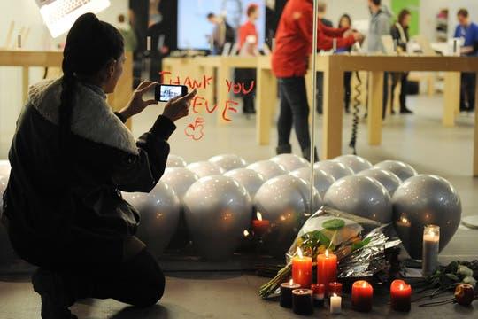 Una mujer rinde homenaje a Steve Jobs en una tienda de Apple en Estados Unidos. Foto: EFE