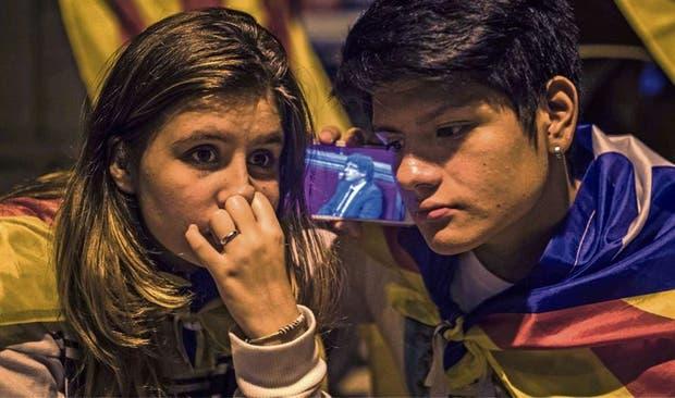 Dos jóvenes independentistas se mantenían expectantes ayer antes del discurso de Puigdemont
