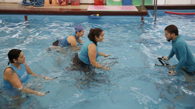 Vanina Delfino (centro) coordina una clase de ciclismo estacionario acuático