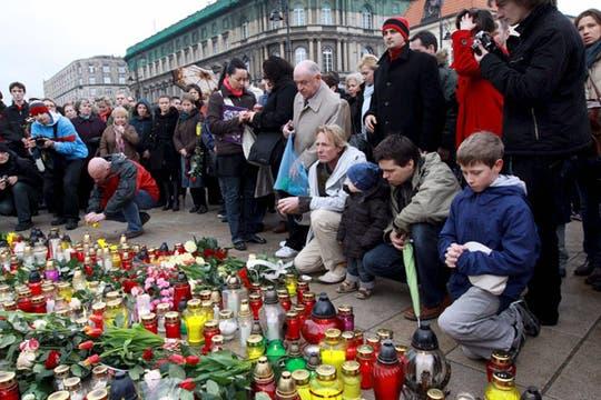 Ciudadanos polacos depositan velas, flores y otras ofrendas ante el Palacio Presidencial de Varsovia. Foto: EFE