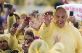 Cubierto por una capa de plástico, el Papa despide a los fieles en Tacloban, luego de dar una emotiva misa