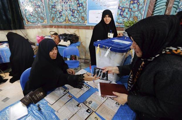 Una mujer emite su voto en un centro electoral de Teherán, durante los decisivos comicios de ayer