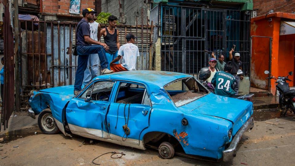 Un grupo de personas permanecen sobre un auto hoy que fue destrozado por los hechos violentos anoche. Foto: EFE / Miguel Gutierrez