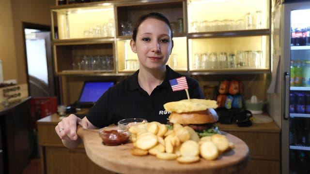 Una cocinera enseña un plato típico estadounidense en el restaurante Rondo en el centro de Sevnica, Eslovenia